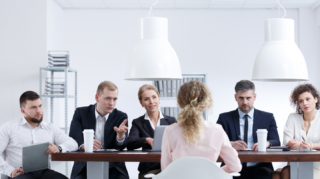 Woman talking to examination board on recruitment review